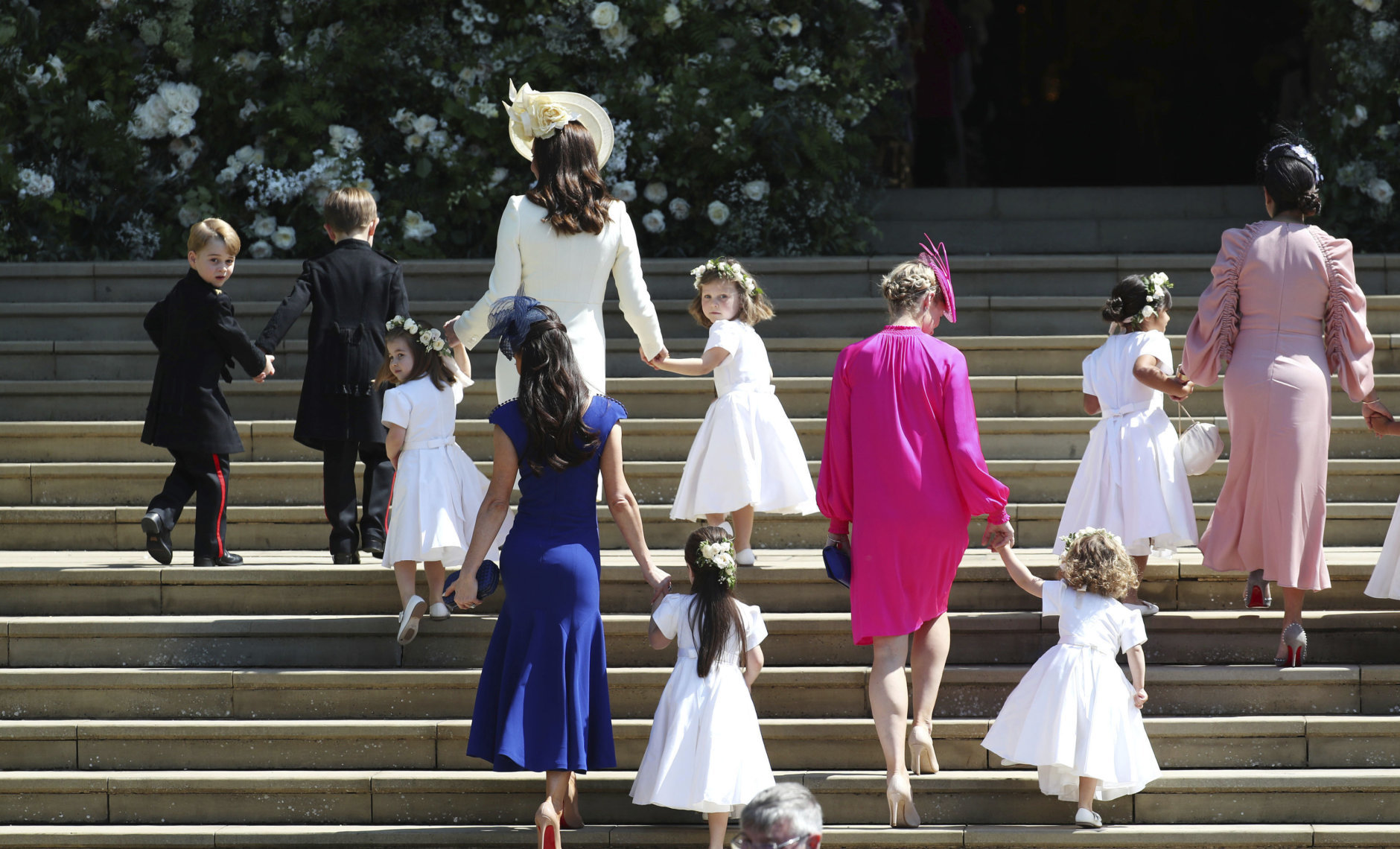 Britain's Prince George, left, Princess Charlotte, third left, Kate, the Duchess of Cambridge, background fourth left and Jessica Mulroney foreground arrive with the bridesmaids and page boys for the wedding ceremony of Prince Harry and Meghan Markle at St. George's Chapel in Windsor Castle in Windsor, near London, England, Saturday, May 19, 2018. (Jane Barlow/pool photo via AP)