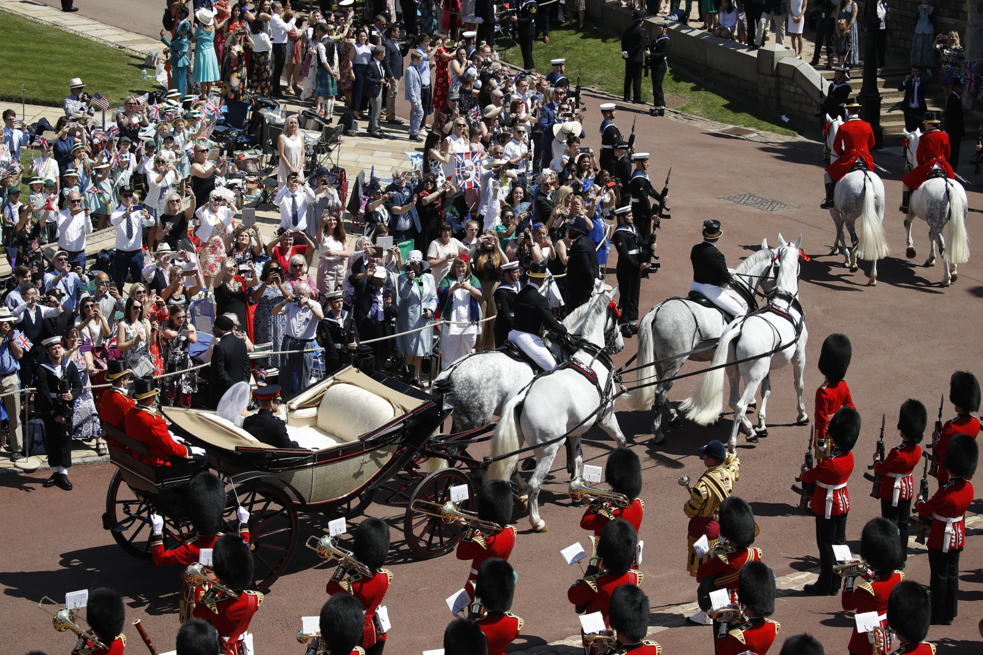 Britain's Prince Harry and Meghan Markle leave in a carriage after their wedding ceremony at St. George's Chapel in Windsor Castle in Windsor, near London, England, Saturday, May 19, 2018. (Odd Andersen/pool photo via AP)