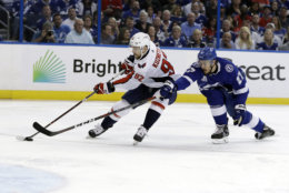Washington Capitals center Evgeny Kuznetsov (92) moves the puck past Tampa Bay Lightning defenseman Ryan McDonagh (27) during the first period of Game 7 of the NHL Eastern Conference finals hockey playoff series Wednesday, May 23, 2018, in Tampa, Fla. (AP Photo/Chris O'Meara)