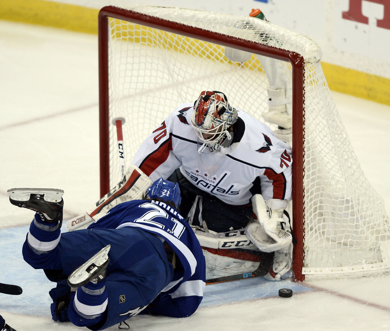 Tampa Bay Lightning center Brayden Point, left, falls in front of Washington Capitals goaltender Braden Holtby as he tries but fails to score during the second period of Game 7 of the NHL Eastern Conference finals hockey playoff series Wednesday, May 23, 2018, in Tampa, Fla. (AP Photo/Jason Behnken)