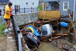 Residents gather by a bridge to look at cars left crumpled in one of the tributaries of the Patapsco River that burst its banks as it channeled through historic Main Street in Ellicott City, Md., on May 28, 2018.  (AP Photo/David McFadden. file)