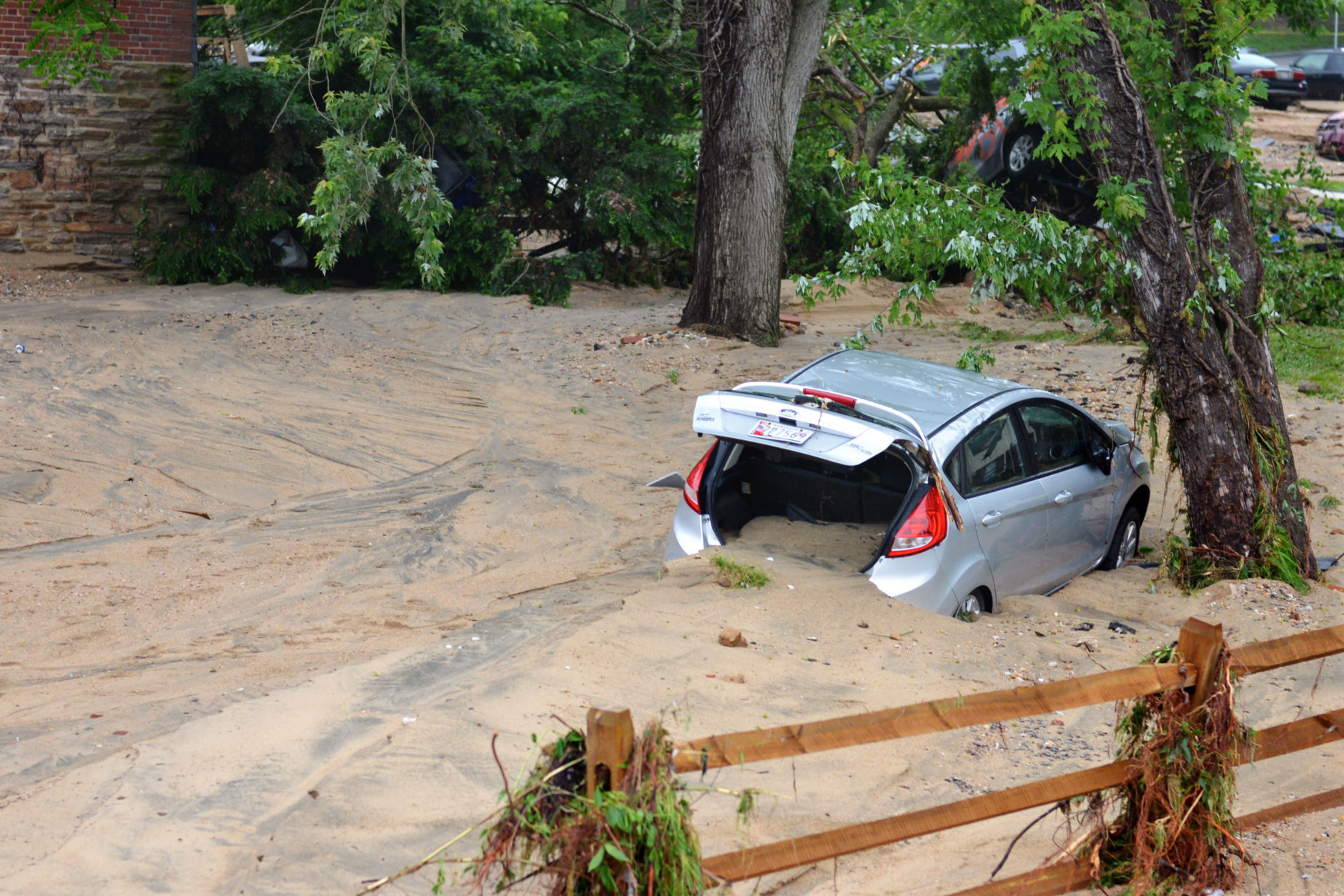 A car that was swept into the riverbank rests just off Main Street in flood-ravaged Ellicott City, Md., Monday, May 28, 2018. Howard County will reopen the closed stretch of a road leading to Main Street on Friday. (AP Photo/David McFadden)