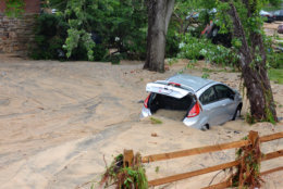 A car that was swept into the riverbank rests just off Main Street in flood-ravaged Ellicott City, Md., Monday, May 28, 2018. Sunday's destructive flooding left the former mill town heartbroken as it had bounded back from another destructive storm less than two years ago. (AP Photo/David McFadden)