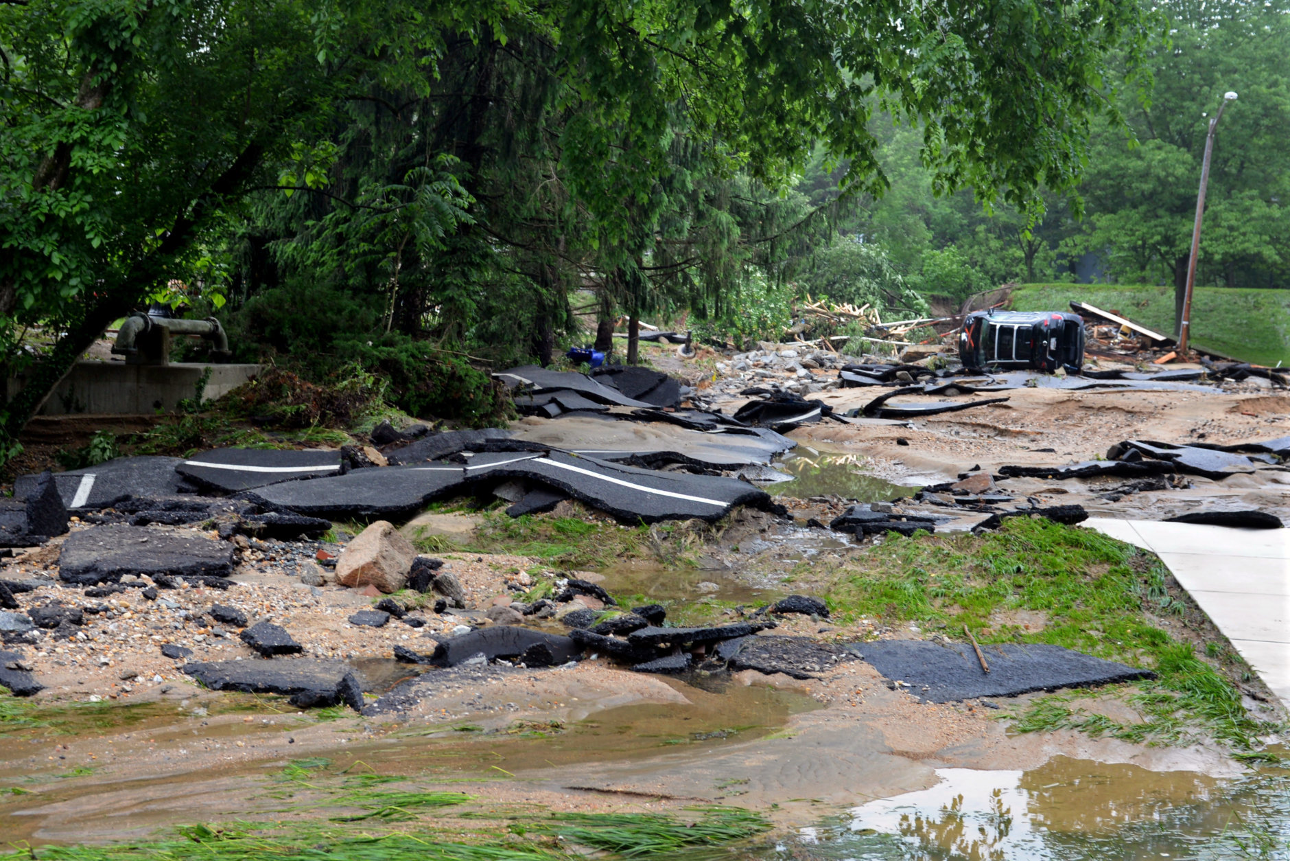 Destroyed chunks of roadway rest after being washed into a riverbed just off Main Street in flood-ravaged Ellicott City, Md., Monday, May 28, 2018. Sunday's destructive flooding left the former mill town heartbroken as it had bounded back from another destructive storm less than two years ago. (AP Photo/David McFadden)