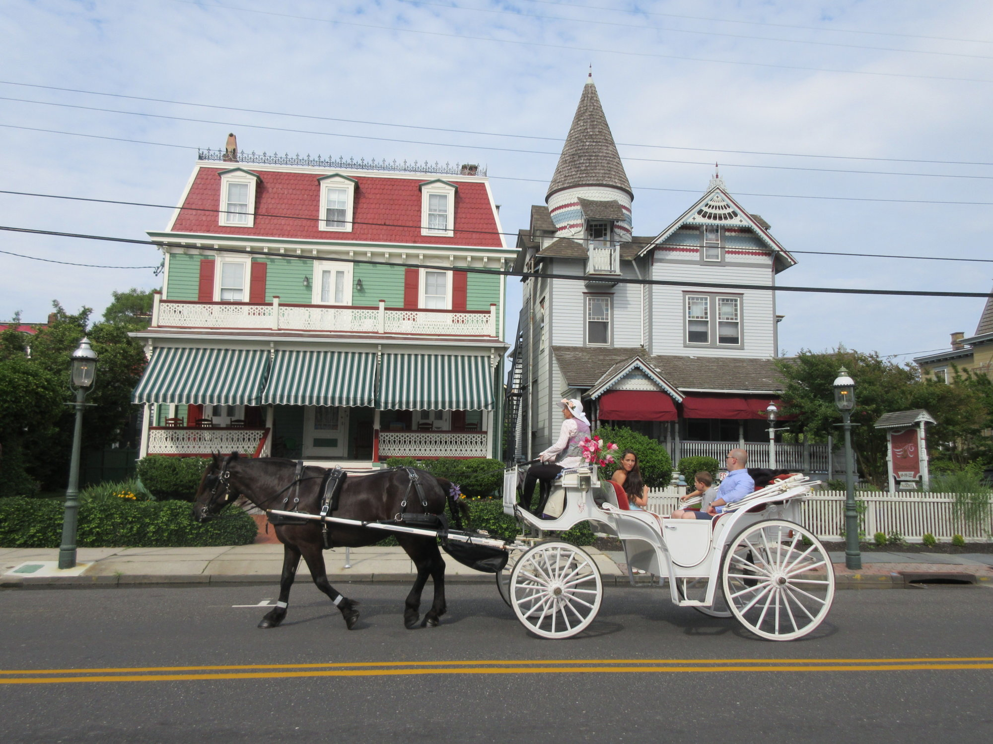 """This June 26, 2015 photo shows visitors taking a horse carriage tour of Cape May, N.J. The city's hundreds of Victorian homes constitute what the National Historic Landmarks program calls """"one of the largest collections of 19th century frame buildings"""" in the United States. Their gables, towers, domes, arched windows and inviting front porches, often trimmed in bright colors, create charming and whimsical streetscapes.  (AP Photo/Beth J. Harpaz)"""