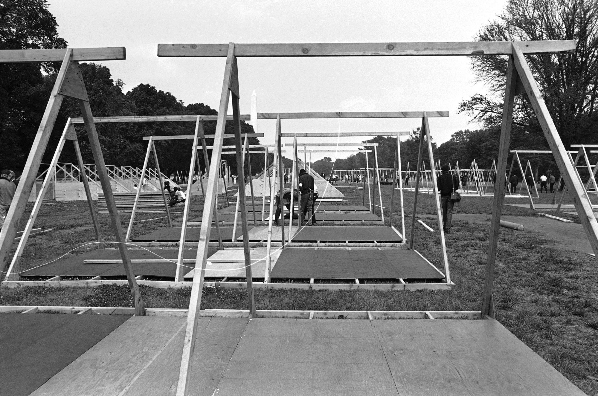 Workmen set up flooring and A-frames for the wooden camp near Lincoln Memorial to house the Poor People's Campaign demonstrators in Washington, May 13, 1968. A federal permit allows the demonstrators to occupy the 15-acre area until on June 16 and limits occupants to 3,000. (AP Photo/Bob Schutz)