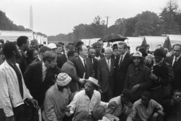 Notables get a conducted tour of Resurrection City, the encampment erected by the Poor Peoples Campaign near the Washington Monument, left background, May 16, 1968. Identifiable at center of group, left to right are Rev. Walter Fauntroy, Wash. D.C. representative of Southern Christian Leadership Conference (left of handheld microphone); Vice President Hubert Humphrey; Mayor Walter Washington of Wash. D.C.; Mayor Ivan Allen Jr. of Atlanta; Mayor John Lindsay of New York City, and Rev. James Bevel of Southern Christian Leadership Conference. (AP Photo/John Rous)