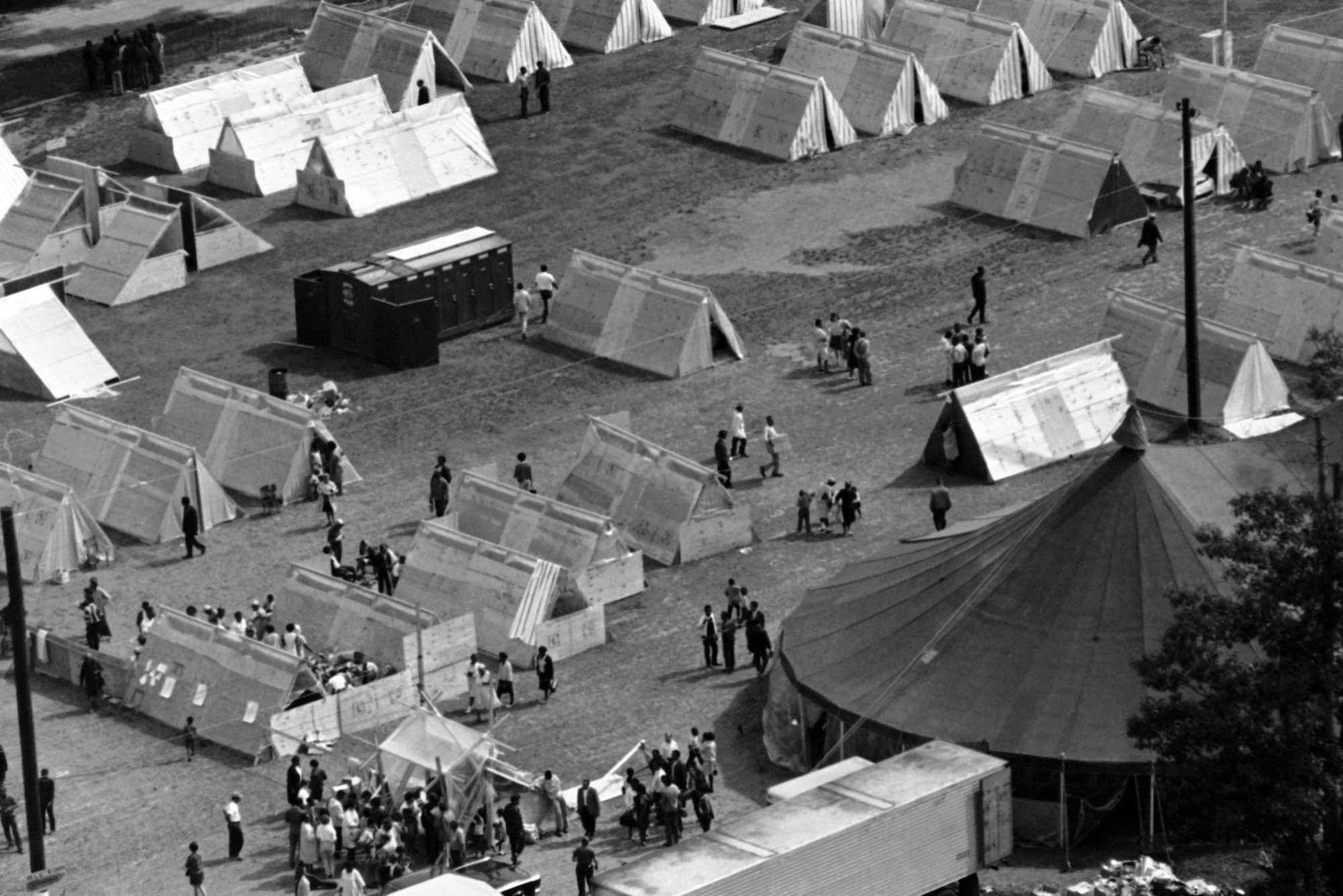 This aerial view shows activity in Resurrection City, the encampment of the Poor People's Campaign in Washington, May 17, 1968. Prefabricated structures in various stages of construction with completed units can be seen at upper right. Large tent in lower right is used as a dining are and general meeting hall for members of the march, sponsored by the Southern Christian Leadership Conference. (AP Photo/Bob Daugherty)