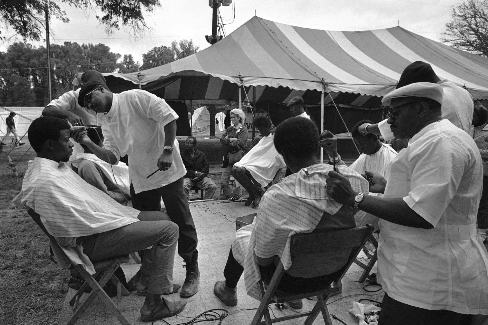 Five barbers go about their task, trimming the hair of some of the residents of Resurrection City in this open-air barber shop, May 20, 1968. (AP Photo/Bob Schutz)