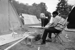 "Monroe Johnson, 13, of Milwaukee, Wisconsin, cooks his mid-day meal outdoors in ""Resurrection City,"" the camp site of the Poor People's Campaign in Washington, May 20, 1968. Another resident shakes a blanket amid the plywood shelters which make up the camp. (AP Photo/Bob Schutz)"