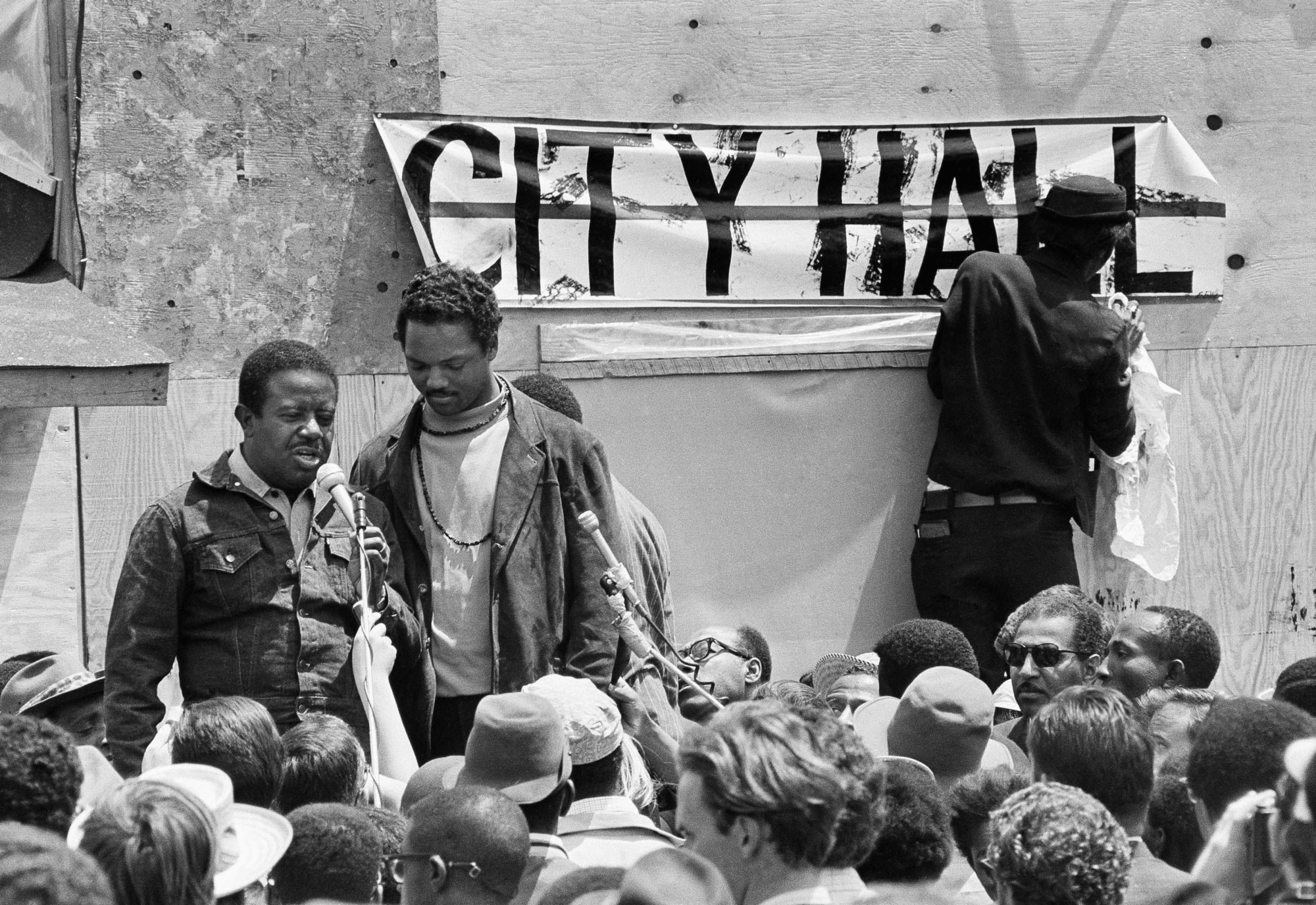 "The Rev. Ralph D. Abernathy, head of the Southern Christian Leadership Conference in Washington D.C.,  May 22, 1968 introduced Resurrection City manager, the Rev. Jesse Jackson of Chicago.   Black leaders gathered at the plywood shelter encampment of the Poor People's Campaign. In background one of the demonstrators nails up a ""City Hall"" sign.  (AP Photo/Charles Tasnadi)"