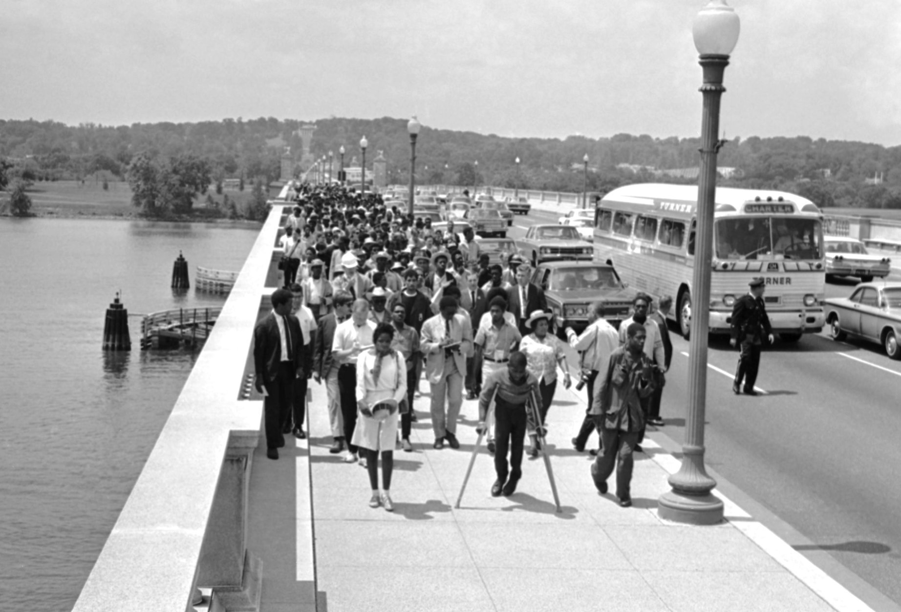 This group of newly-arrived demonstrators of the Poor People's Campaign walk across Memorial Bridge, spanning the Potomac River, May 22, 1968, to the plywood encampment at Resurrection City, USA. The new arrivals who have been staying in Northern Virginia churches since Sunday, are from Alabama, Mississippi, Georgia, North Carolina and Virginia. In background high on the slope of Arlington National Cemetery is the Lee Mansion. (AP Photo/Charles Tasnadi)