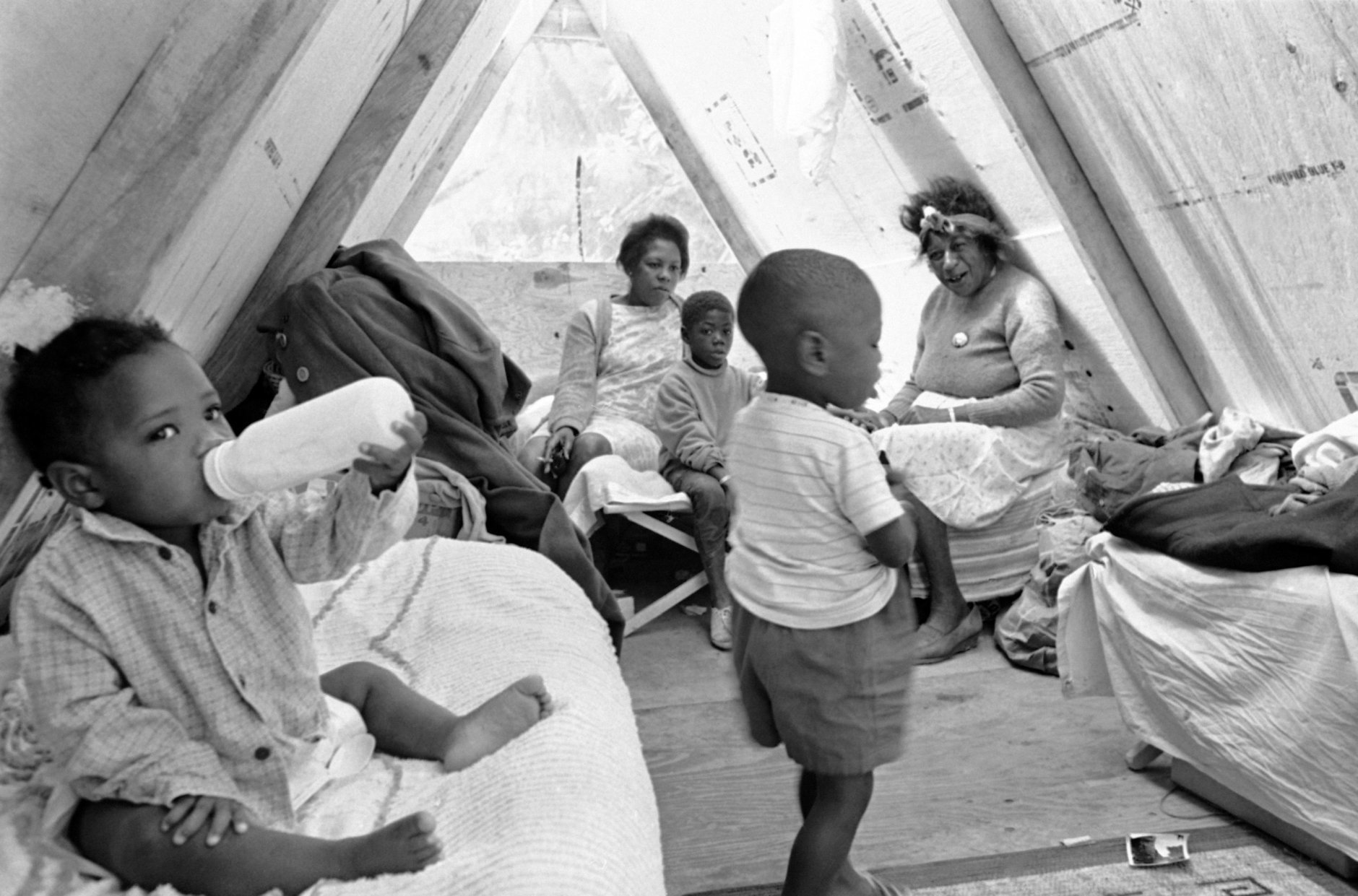 These Mississippians, including one-year-old Debbie Shirley with her nursing bottles made themselves at home in Resurrection City, Washington, May 22, 1968. In foreground is Michael Lee, 3. In background, from left, are: Francis Nunn of Crenshaw, Miss., Jerry Davis, 7, and Edith Maydukes of Marks, Miss. (AP Photo/Charles Tasnadi)