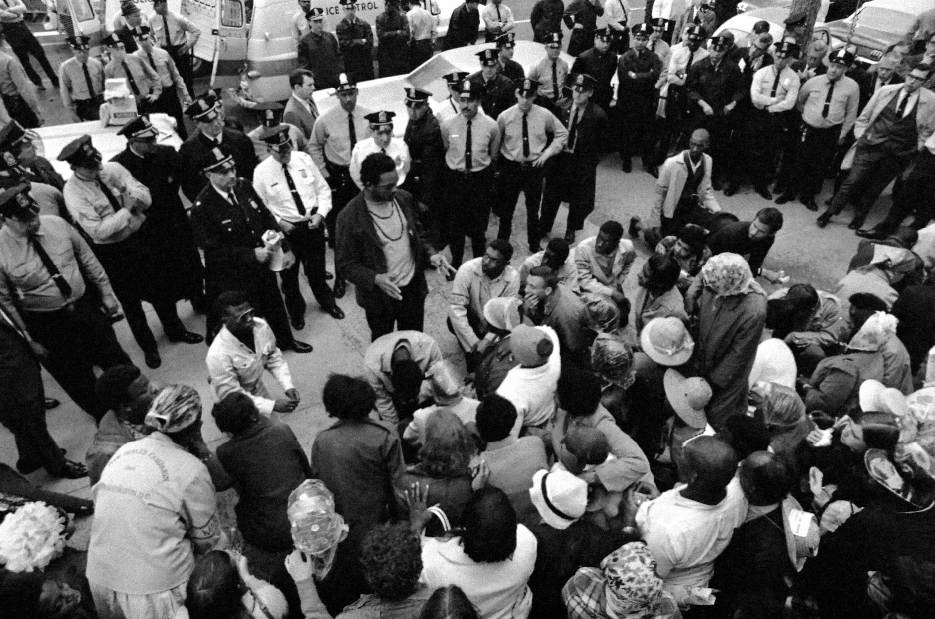 With police standing by, the Rev. Jesse Jackson talks to Poor People's Campaign demonstrators outside of the Capitol in Washington, May 23, 1968. After the arrest of approximately 20 of the demonstrators, Jackson who is Resurrection City manager, told his followers to leave and meet with him inside the Rayburn House Office Building. Jackson said he had a permit for the meeting. (AP Photo/Bob Daugherty)