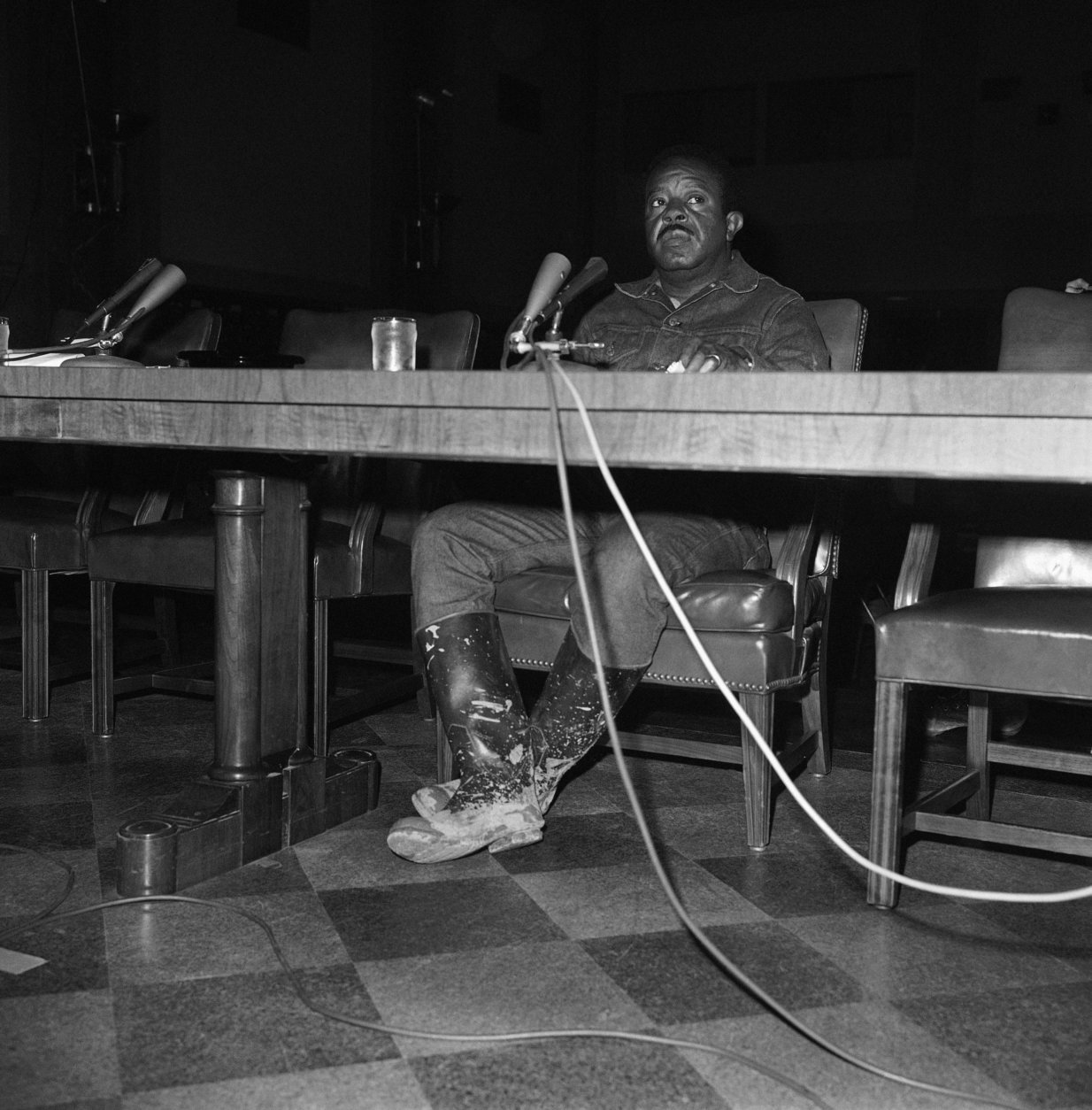 The Rev. Ralph Abernathy, head of the Southern Christian Leadership conference and leader of the Poor People's Campaign, displayed mud-caked boots as he testified in Washington on May 29, 1968 before a Senate subcommittee on manpower, poverty and employment. Before testifying, Abernathy had been at Resurrection City, which is covered with ankle deep mud after two days of rain. (AP Photo/Henry Griffin)