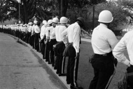 A line of helmeted police stand shoulder to shoulder just outside an entrance to Resurrection City, the encampment of the Poor People's Campaign in Washington, June 24, 1968. The permit allowing the encampment ended last night and police were on hand to clear out any residents who remain. (AP Photo/Bob Daugherty)
