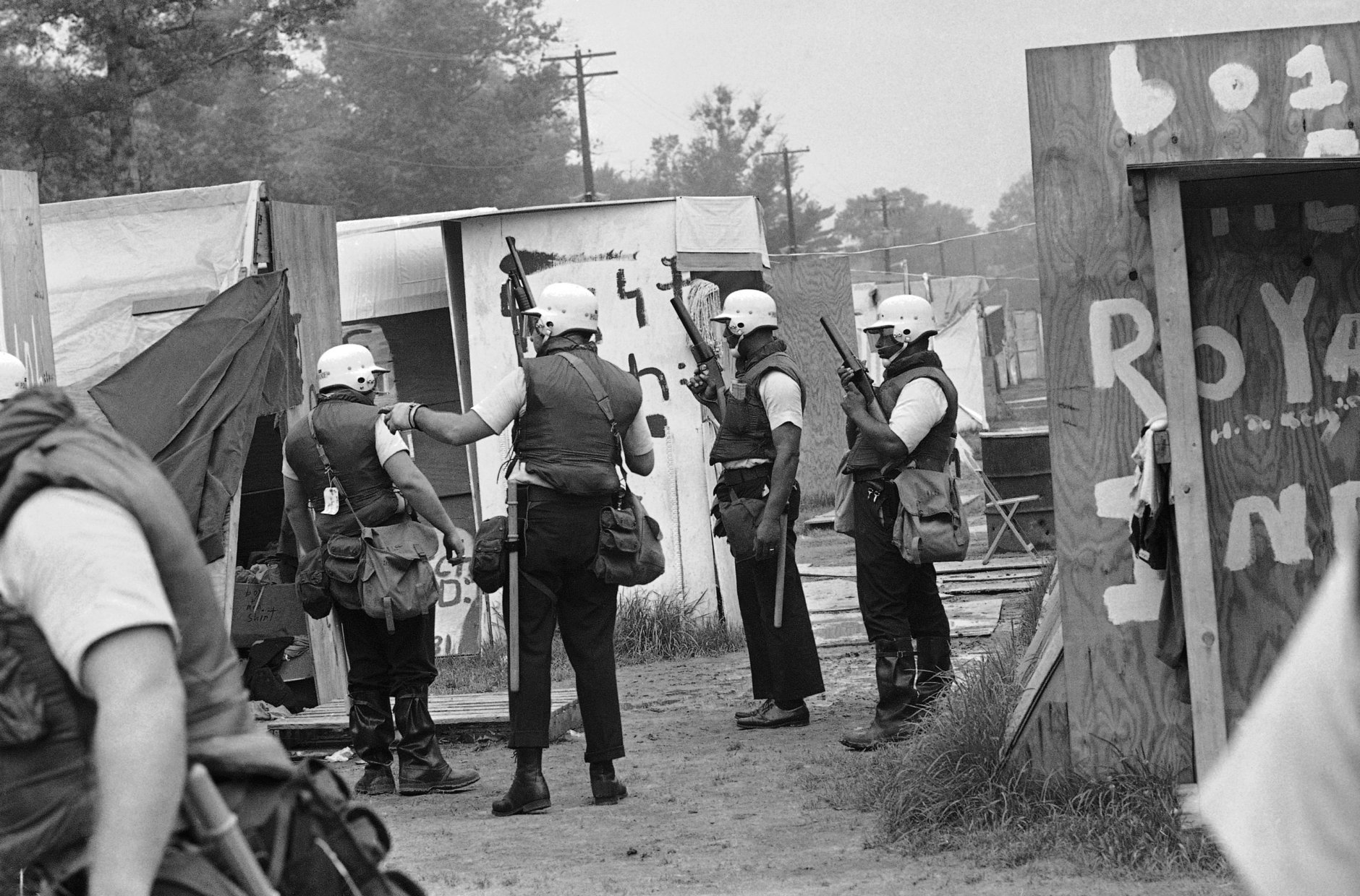 Heavily armed and wearing protective clothing, police move through Resurrection City, the camp of the Poor People's Campaign, clearing the area of all residents in Washington, June 24, 1968. Their permit to camp on Federal Park land expired on June 23. (AP Photo/Charles Harrity)