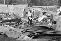 The possessions of former residents of Resurrection City are left on the flooring as the plywood and plastic shanties of the Poor People's Campaign are dismantled by workmen, June 25, 1968. Plywood sections are being loaded on trucks to be carted away. The possessions will be cataloged by tent and stored. (AP Photo/Bob Daugherty)