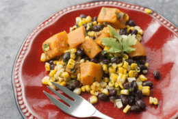 This May 5, 2014, photo shows sweet potato, grilled corn and black bean salad with spicy cilantro dressing in Concord, N.H. This recipe swaps sweet potatoes for the more traditional white potatoes and loses the standard recipe's abundant mayonnaise in favor of a dressing high in flavor and low in fat. (AP Photo/Matthew Mead)