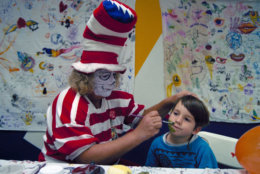 Wavy Gravy, costumed as The Cat in the Hat, paints the face of 5-year-Old Jesse James Nugent backstage at the Oakland Coliseum during a Grateful Dead concer February 14, 1993.  Gravy, a backstage presence since the 1960s, entertains kids in the daycare room set up for the children of the band members and crew. (AP Photo/Eric Risberg)