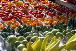 Fresh-picked tomatoes, cucumbers and other summer garden vegetables are displayed for sale at a farmers market in Falls Church, Va., Saturday, Aug. 8, 2015. (AP Photo/J. Scott Applewhite)