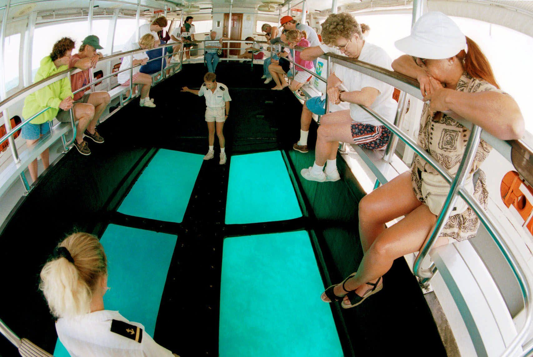 Tourists aboard the ship San Jose listen to tour guide Scott Buckley, standing by glass bottom, describe fish and features in the coral reef in Key Largo, Fla., at John Pennekamp Coral Reef State Park, Tuesday, Feb. 2, 1999. The ship holds 98 passengers and makes 3 trips to the coral reef 6.5 miles from the shore of the park. A new boat coming this spring will hold 150 passengers. Well over 100,000 people take the glass bottom boat tour every year. Along with the glass bottom boats they also have 3 snorkle boats the take approx. 60,000 snorklers and divers to the reef throughout the year.  (AP Photo/Mickey Krakowski)