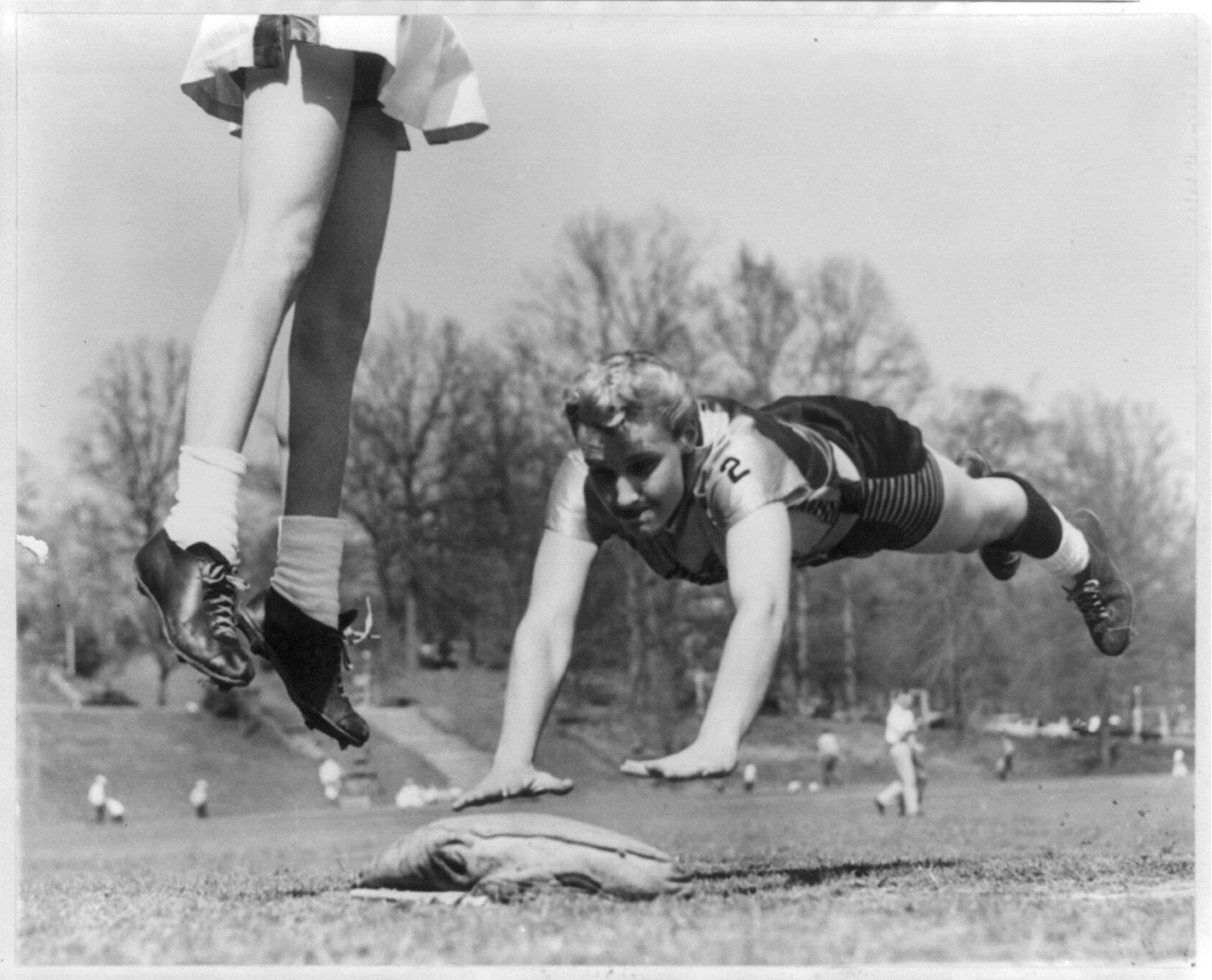 Photograph shows Linda McConkey, of the Lorelei Ladies softball team, diving for third base during an exhibition game; also shows the legs of Jerrie Rainey, playing third base for the Atlanta Tomboys, as she jumps for the ball in Atlanta, Georgia. (Courtesy: Library of Congress)