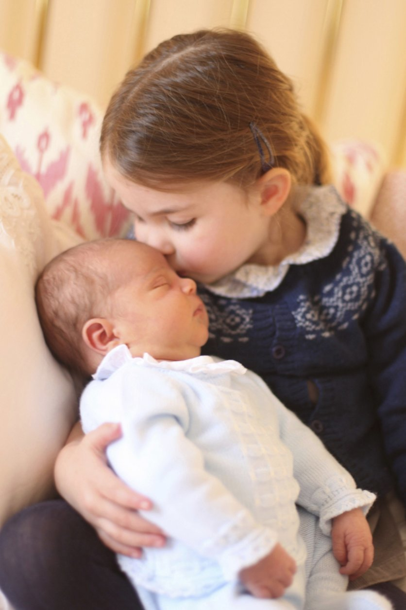 In this May 2, 2018 photograph provided by Kensington Palace, Britain's Princess Charlotte cuddles her brother Prince Louis, on her third birthday, at Kensington Palace, in London. Prince William and his wife Kate have released two pictures documenting the early days of Britain's newest prince. (Duchess of Cambridge/via AP)