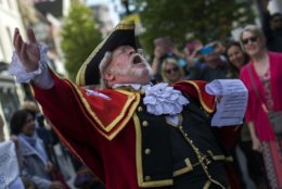 A town crier announces the wedding to the crowd in Windsor, England, Friday, May 18, 2018. Preparations continue in Windsor ahead of the royal wedding of Britain's Prince Harry and Meghan Markle Saturday May 19. (AP Photo/Emilio Morenatti)