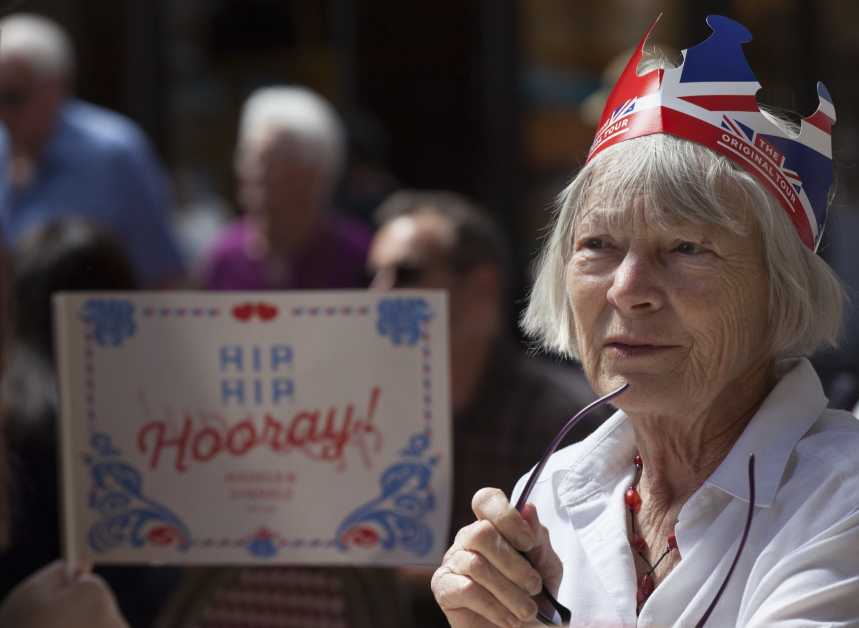 "A woman looks up to a person holding a small flag reading ""Hip Hip Hooray"" as they sit on a terrace near Windsor castle, England, Friday, May 18, 2018. Preparations continue in Windsor ahead of the royal wedding of Britain's Prince Harry and Meghan Markle Saturday May 19. (AP Photo/Peter Dejong)"