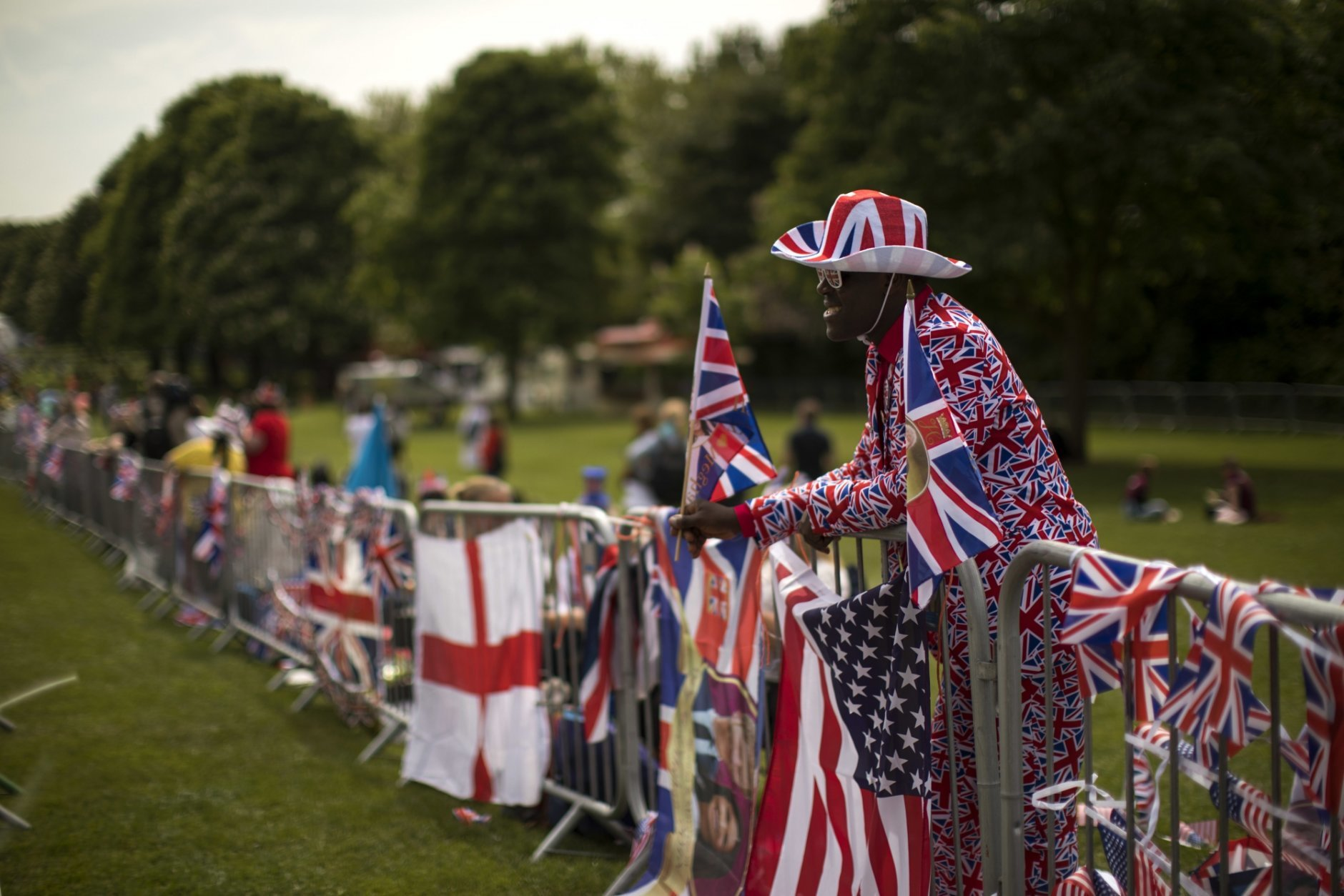 Joshua Arane from Battersea stands on the security fence on the Long walk ahead of the wedding of Prince Harry and Meghan Markle in Windsor, England, Friday, May 18, 2018. Preparations continue in Windsor ahead of the royal wedding of Britain's Prince Harry and Meghan Markle Saturday May 19. (AP Photo/Emilio Morenatti)