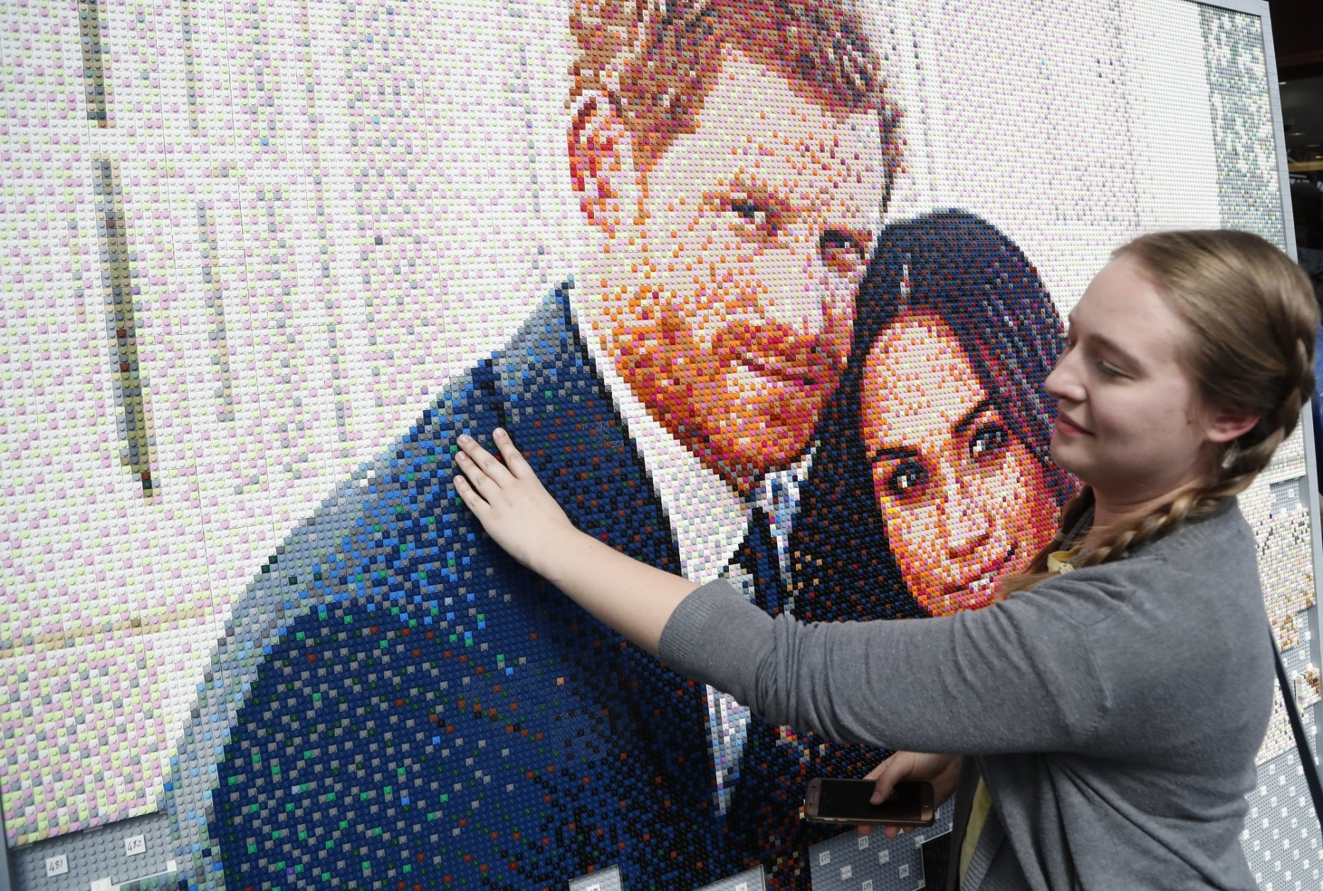 People put bricks in a mosaic of the royal couple in a shopping mall in Windsor, England, Friday, May 18, 2018. Preparations continue in Windsor ahead of the royal wedding of Britain's Prince Harry and Meghan Markle Saturday May 19. (AP Photo/Frank Augstein)