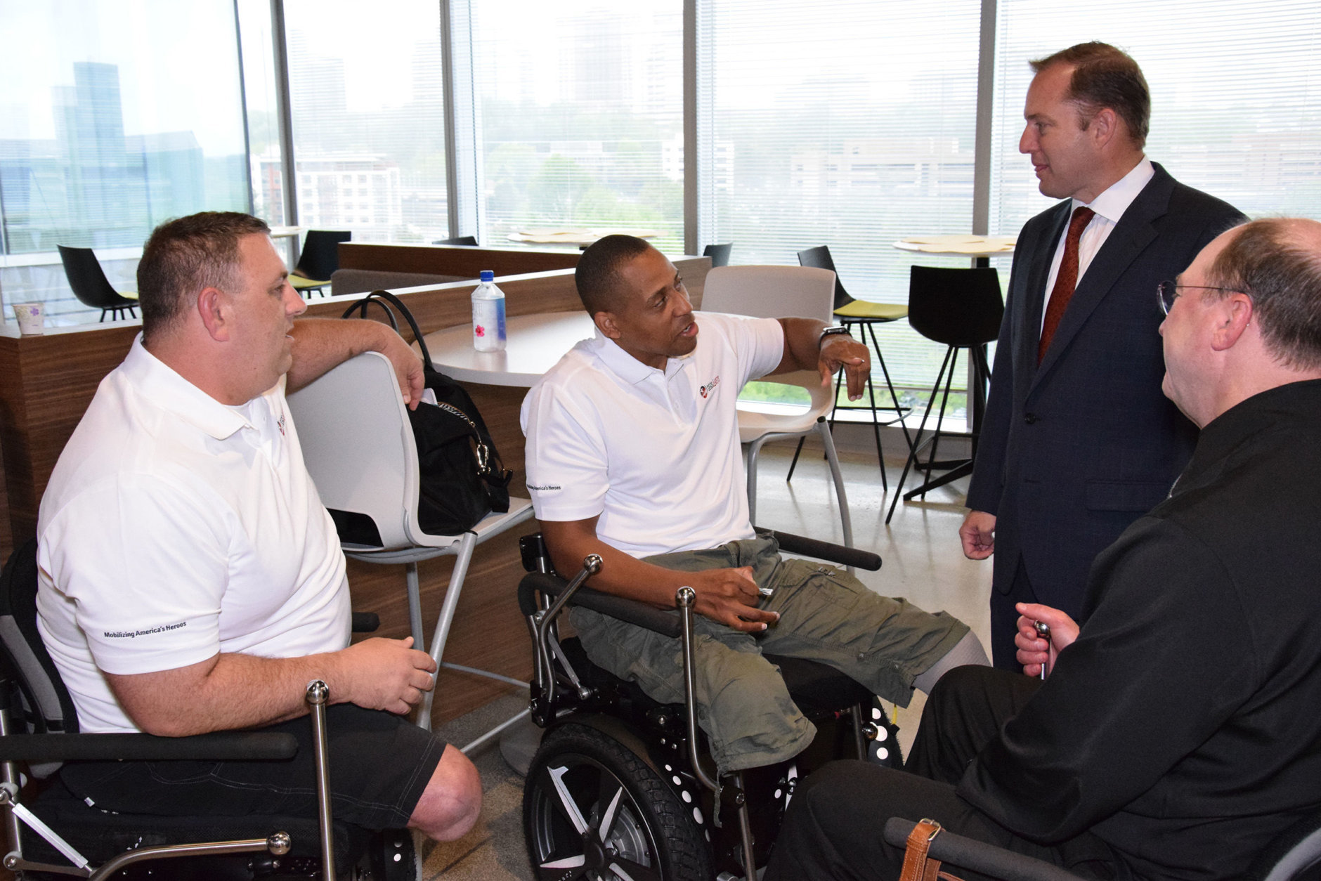 Pictured here are recipients of Segway chairs, funded by the PenFed Foundation: from left, Staff Sgt. Dustin Tuller and retired Master Sgt. Cedric King talk with PenFed President and CEO James Schenck and Jerry Kerr of Seg4Vets, far right. (Courtesy PenFed)
