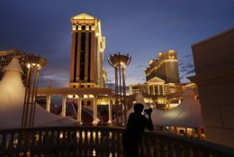 """FILE - In this Monday, Jan. 12, 2015 file photo, a man takes pictures of Caesars Palace hotel and casino, in Las Vegas. The union representing thousands of housekeepers in Las Vegas says Caesars Entertainment has rejected a proposal to include language in a new contract to protect workers if a """"Do Not Disturb"""" sign has been hanging on a doorknob more than 24 hours. The Culinary Union on Wednesday, May 2, 2018, said under its proposal, security would open a room """"for entry and service"""" if a guest refuses housekeeping for more than 24 hours. Caesars previously announced security would begin checking rooms every 24 hours, even if the sign is hanging on the doorknob. (AP Photo/John Locher, File)"""