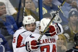 Washington Capitals' Andre Burakovsky, left, gets a hug from teammate John Carlson (74) after scoring a goal against the Tampa Bay Lightning during the second period of Game 7 of the NHL Eastern Conference finals hockey playoff series Wednesday, May 23, 2018, in Tampa, Fla. (AP Photo/Jason Behnken)