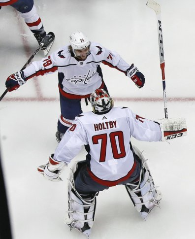 0f4e29955b2 ... Holtby (70) joins the celebration with a hug from Nathan Walker (79)  after Evgeny Kuznetsovs  game-winning goal during the overtime period in Game  6 of ...