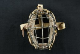 Early Catcher's Mask  With a well-earned fear of foul tips ricocheting off his head, Harvard's Alexander Tyng wore a converted fencer's mask for a game in 1877, becoming the first-known player to don a catcher's mask. Only a year later, the patented headgear appeared in Spalding's sporting goods catalog and professional catchers began wearing masks. Modest modifications followed, such as additional padding and buckled straps. Charles Arnold, a student at Phillips Academy and Yale, used this mask from 1905 to 1914. Charles Arnold's catcher's mask, 1905. Canvas, leather, and metal. Courtesy of the National Baseball Hall of Fame and Museum (082.00.00)