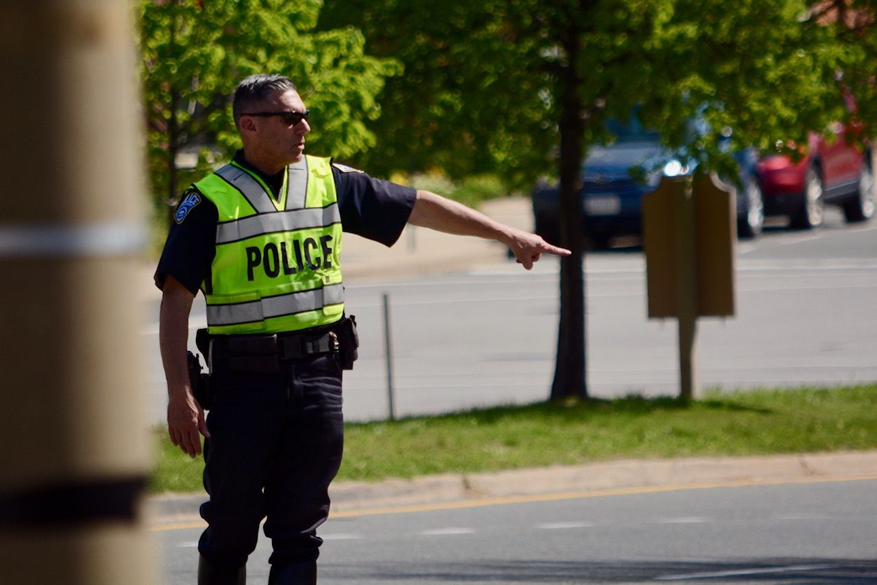 Arlington County Police stop drivers who appeared to fail to yield to an undercover officer in a crosswalk on Fairfax Drive. (WTOP/Dave Dildine)