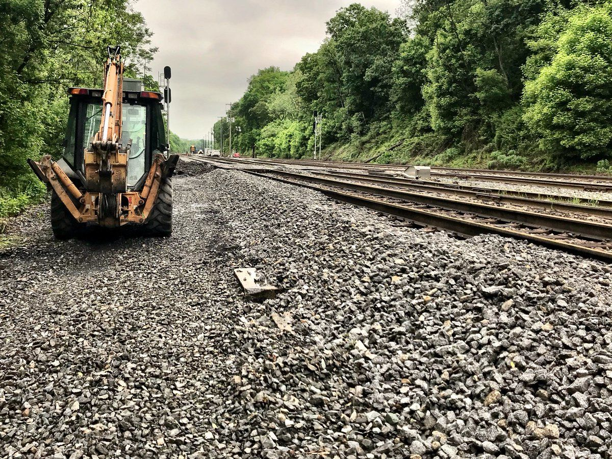 Tons of gravel in dump trucks have been replaced along flooded tracks. (WTOP/Neal Augenstein)