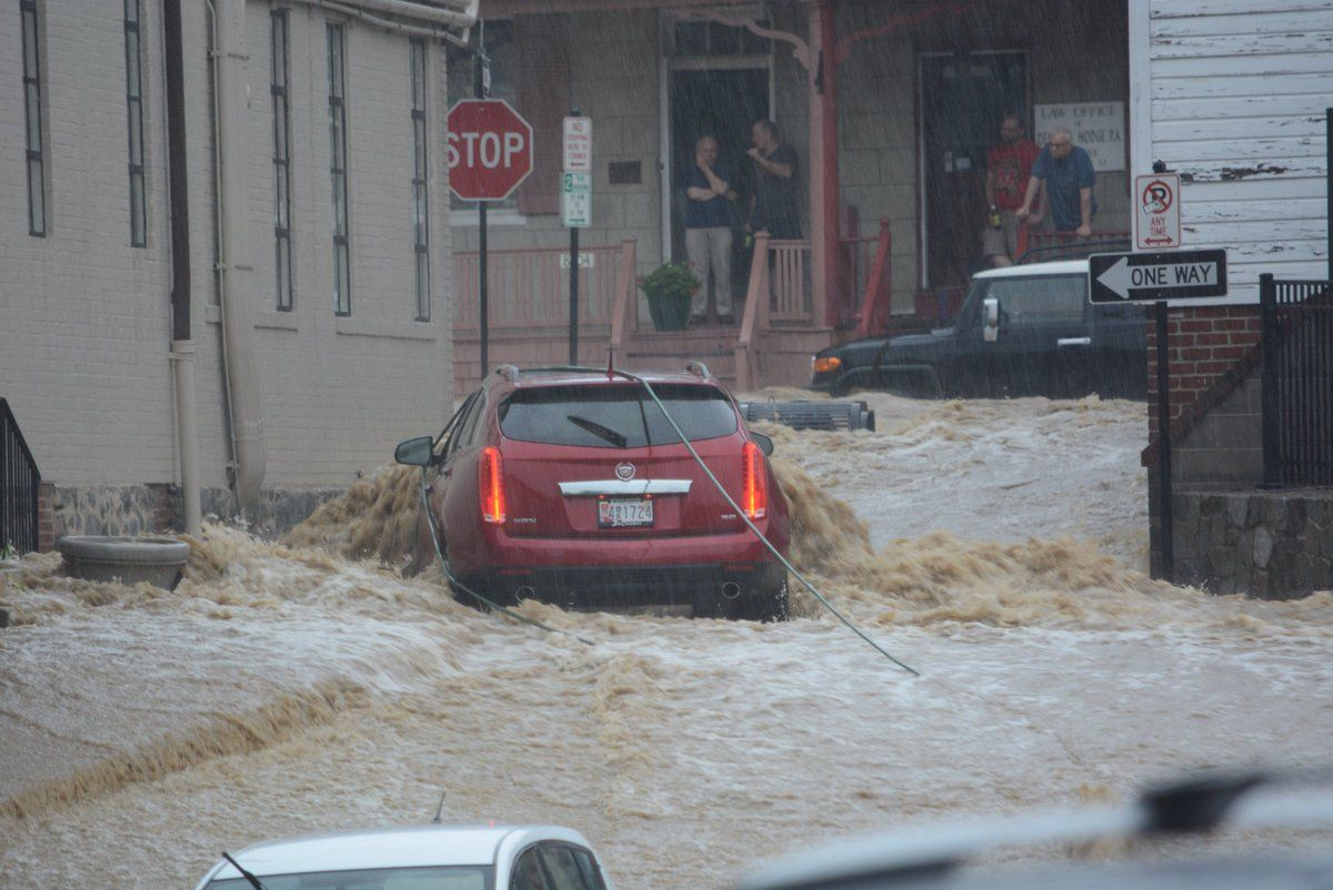 A red vehicle abandoned in floodwaters