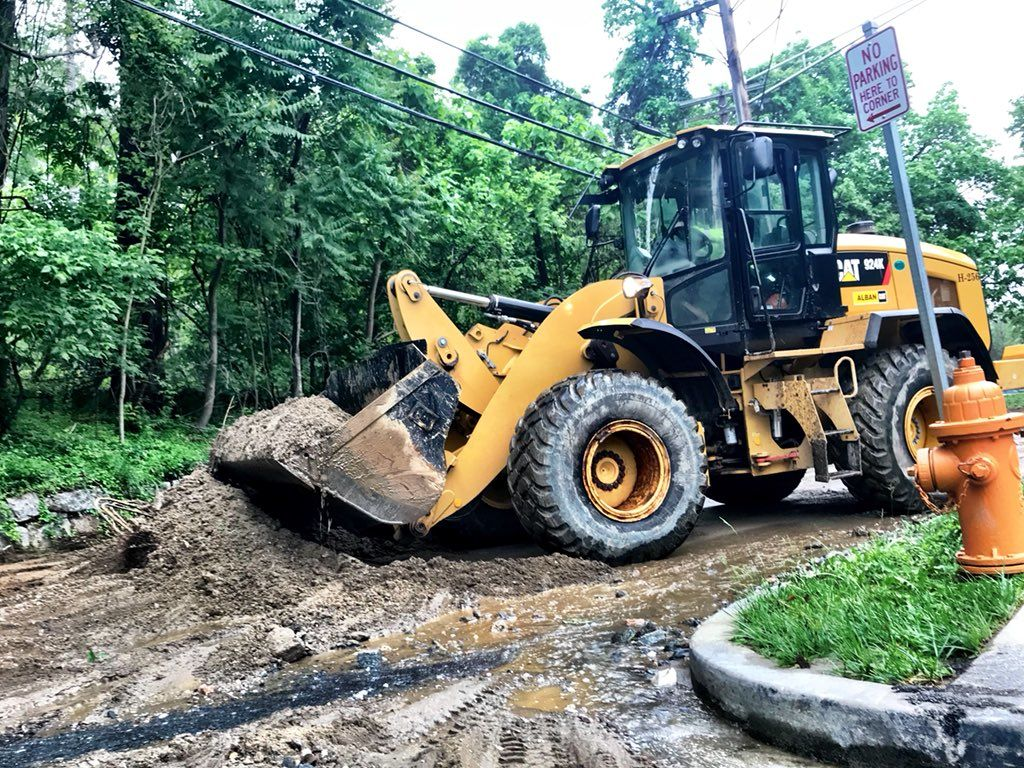 Several dump trucks are scooping mud off Fels Lane, near Ellicott Mills Drive after the flooding in Ellicott City. (WTOP/Neal Augenstein)