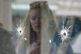 FILE- In this May 24, 2014, file photo, a woman looks at the bullet holes on the window of IV Deli Mark where a mass shooting took place near the University of California, Santa Barbara campus, in the Isla Vista beach community. In response to the killing rampage of Elliot Rodger, 22, that left seven people, including himself dead, lawmakers approved and California Gov. Jerry Brown signed a law which requires law enforcement agencies to develop policies that encourage officers to search the state's database of gun purchases as part of routine welfare checks. More than 900 laws approved by the Legislature and signed by the governor will take effect Jan. 1, 2015. (AP Photo/Jae C. Hong, File)