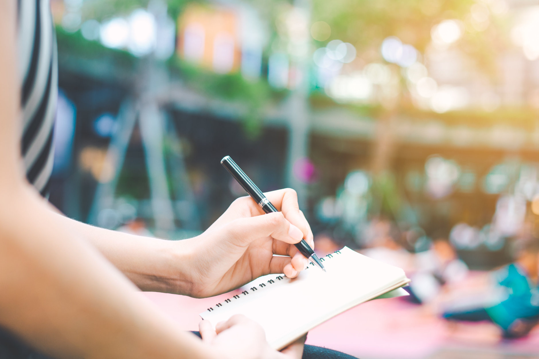 The woman's hand is writing on a blank notepad with a pen.