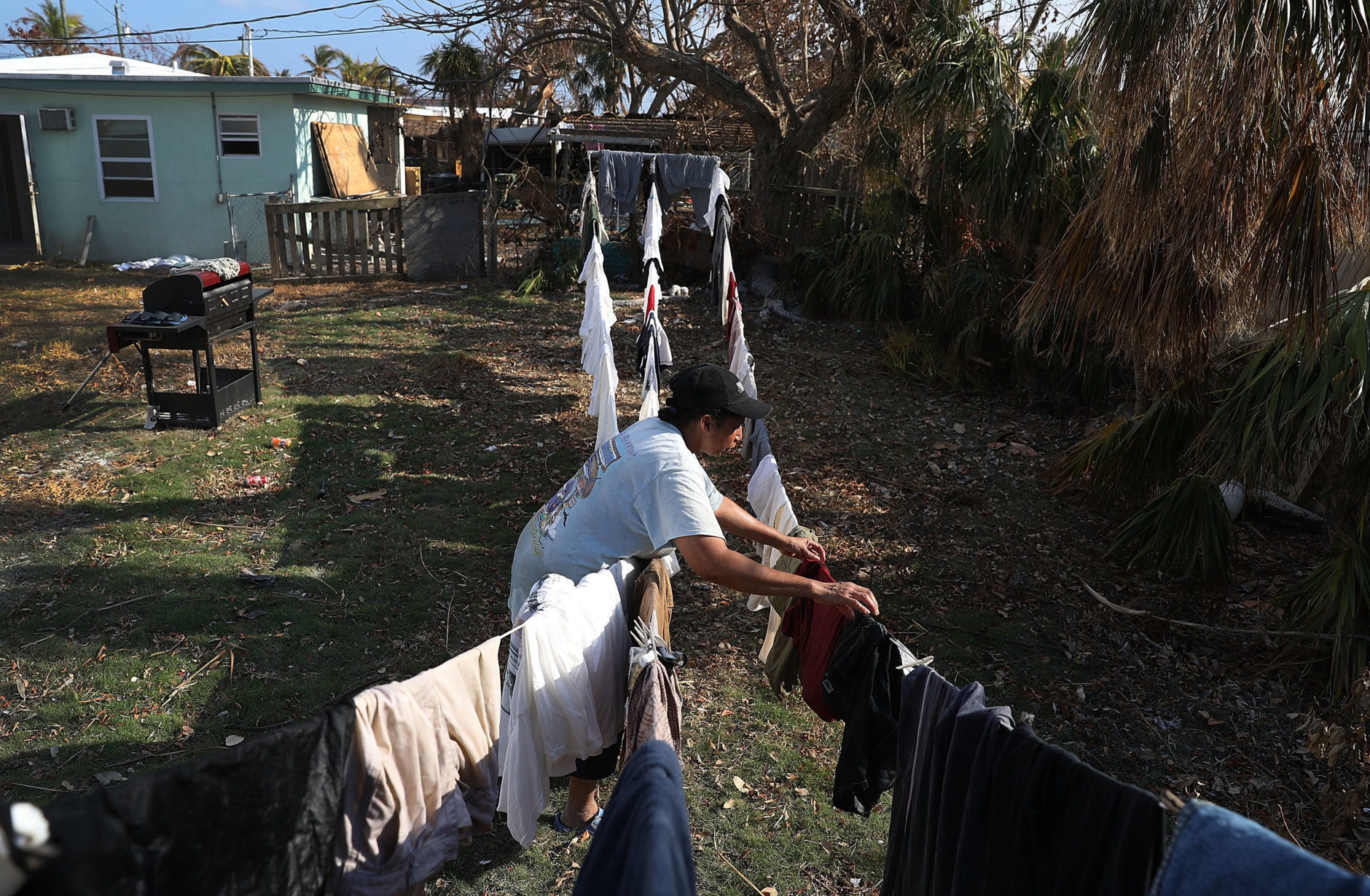 MARATHON, FL - SEPTEMBER 19:  Patricia Spencer hangs up laundry as she tries to salvage what she can from her home after it was damaged by hurricane Irma on September 19, 2017 in Marathon, Florida.  The process of rebuilding has begun as the Federal Emergency Management Agency has reported that 25-percent of all homes in the Florida Keys were destroyed and 65-percent sustained major damage when they took a direct hit from Hurricane Irma.  (Photo by Joe Raedle/Getty Images)