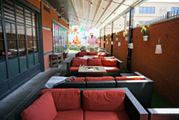 Hazel boasts a fun & funky patio complete with astroturf, potted plant-lined brick walls, broad wicker seating, and fire pits to keep guests cozy in cooler temperatures. A bright, hand-painted floral mural serves as the centerpiece of the urban garden oasis. This summer, enjoy table side Spritz service via a roving cocktail cart. (Courtesy Hazel)