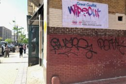Graffiti mars the side of a red brick building in Columbia Heights. (WTOP/John Aaron)