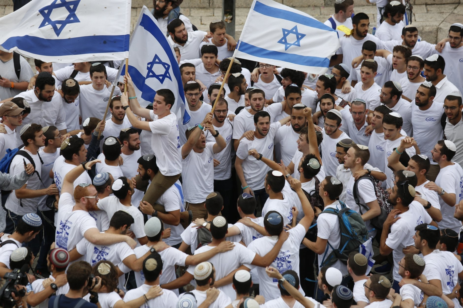 Israeli youths wave national flags outside the Old City's Damascus Gate, in Jerusalem, Sunday, May 13, 2018. Israel is marking the 51st anniversary of its capture of east Jerusalem in the 1967 Middle East war. (AP Photo/Ariel Schalit)