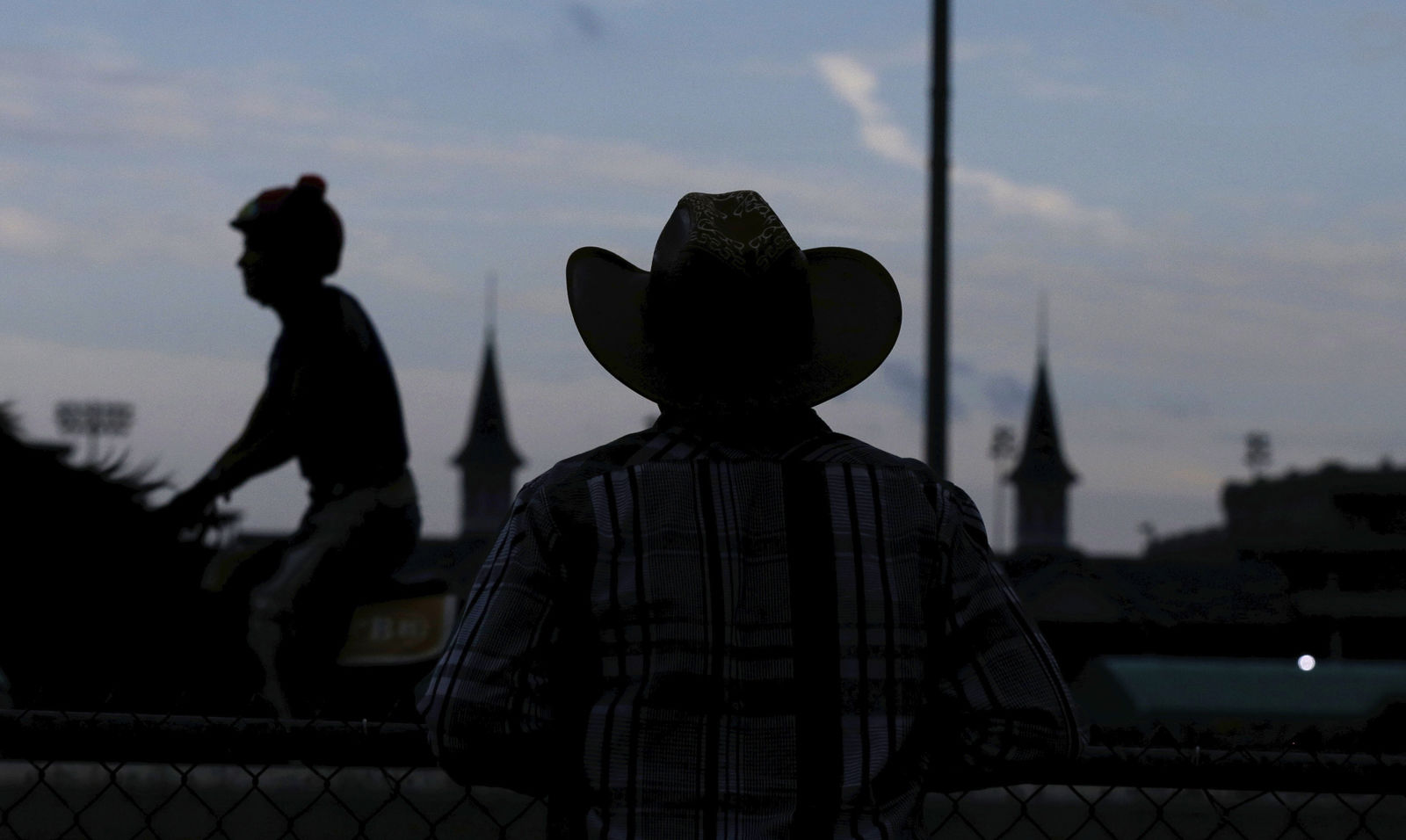 A worker watches during morning workouts at Churchill Downs Friday, May 4, 2018, in Louisville, Ky. The 144th running of the Kentucky Derby is Saturday, May 5th. (AP Photo/Kiichiro Sato)