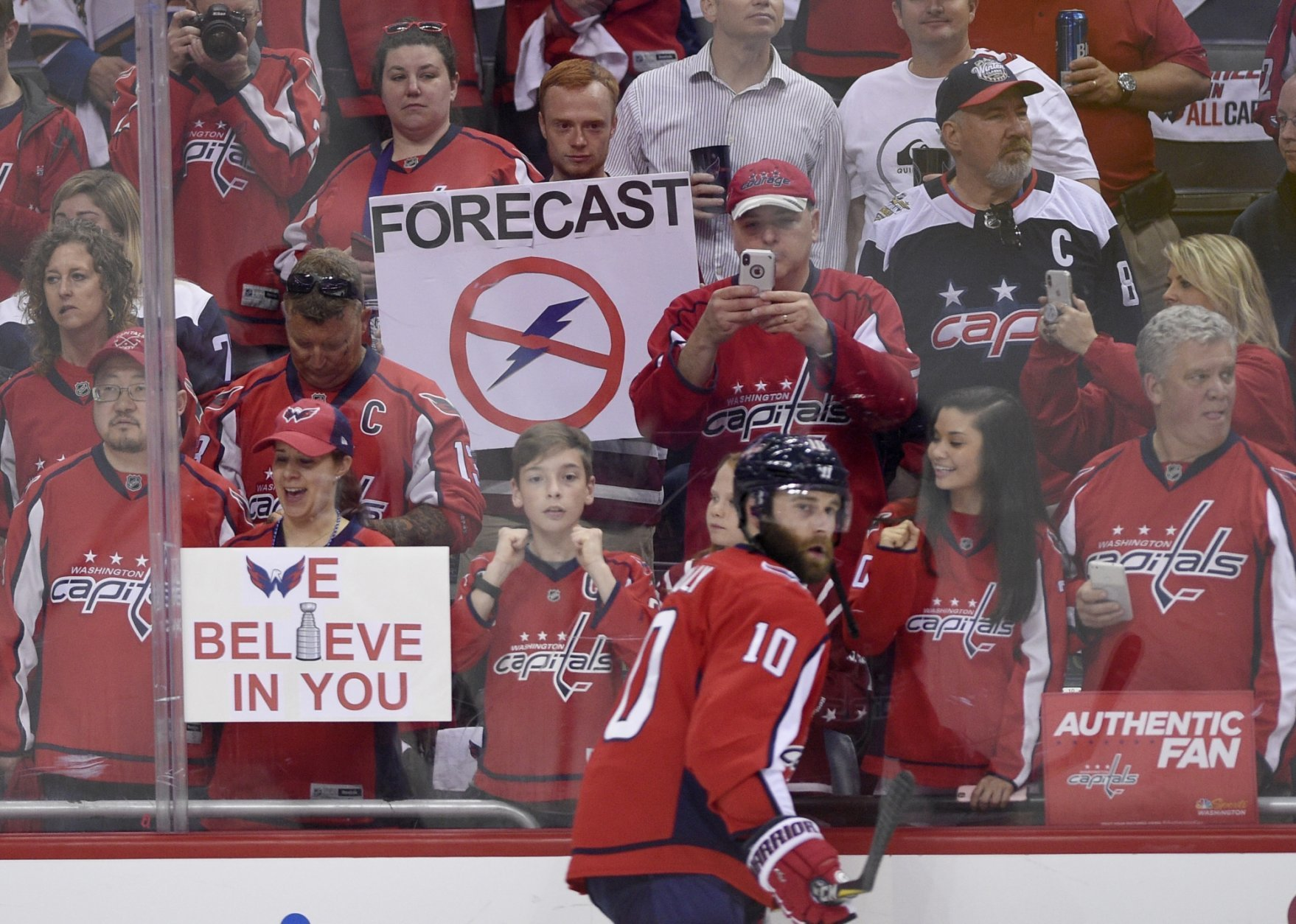 Washington Capitals fans hold up signs during warm ups before Game 3 of the NHL Eastern Conference finals hockey playoff series between the Washington Capitals and the Tampa Bay Lightning, Tuesday, May 15, 2018 in Washington. Also seen is Washington Capitals right wing Brett Connolly (10). (AP Photo/Nick Wass)