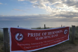 "In anticipation of the June 2019 performance in France, band mom Margaret Jamborsky brought the band's banner to Utah Beach, the site of the U.S. Navy Memorial, dedicated to the more than 1,000 sailors who died there.   ""The USS Herndon would have been right in the center of the picture on D-Day,"" Jamborsky said. ""It was quite moving to see such a beautiful, serene place, a far cry from what it would have looked like that day in 1944."" (Courtesy Margaret Jamborsky)"